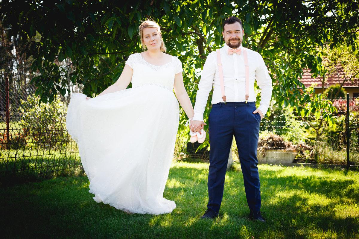 Nevěsta se ženichem se drží za ruce, svatební portrét