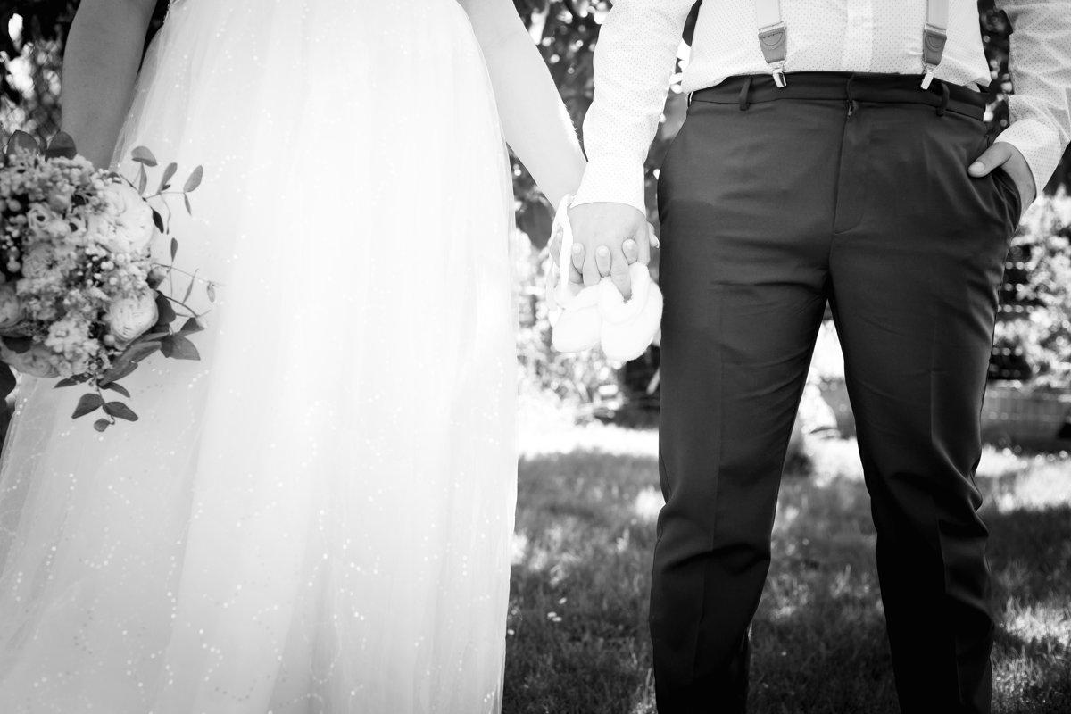 Detail na ruce nevěsty a ženicha, jak drží dětské botičky