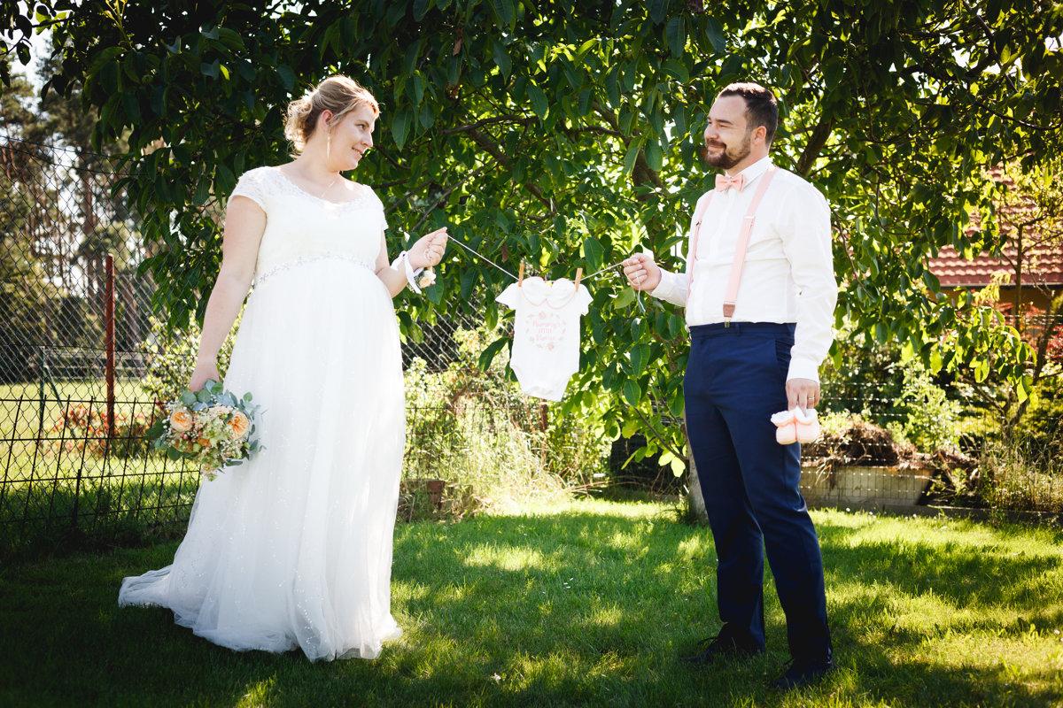 Portrét nevěsty a ženicha jak drží dětské bodýčko