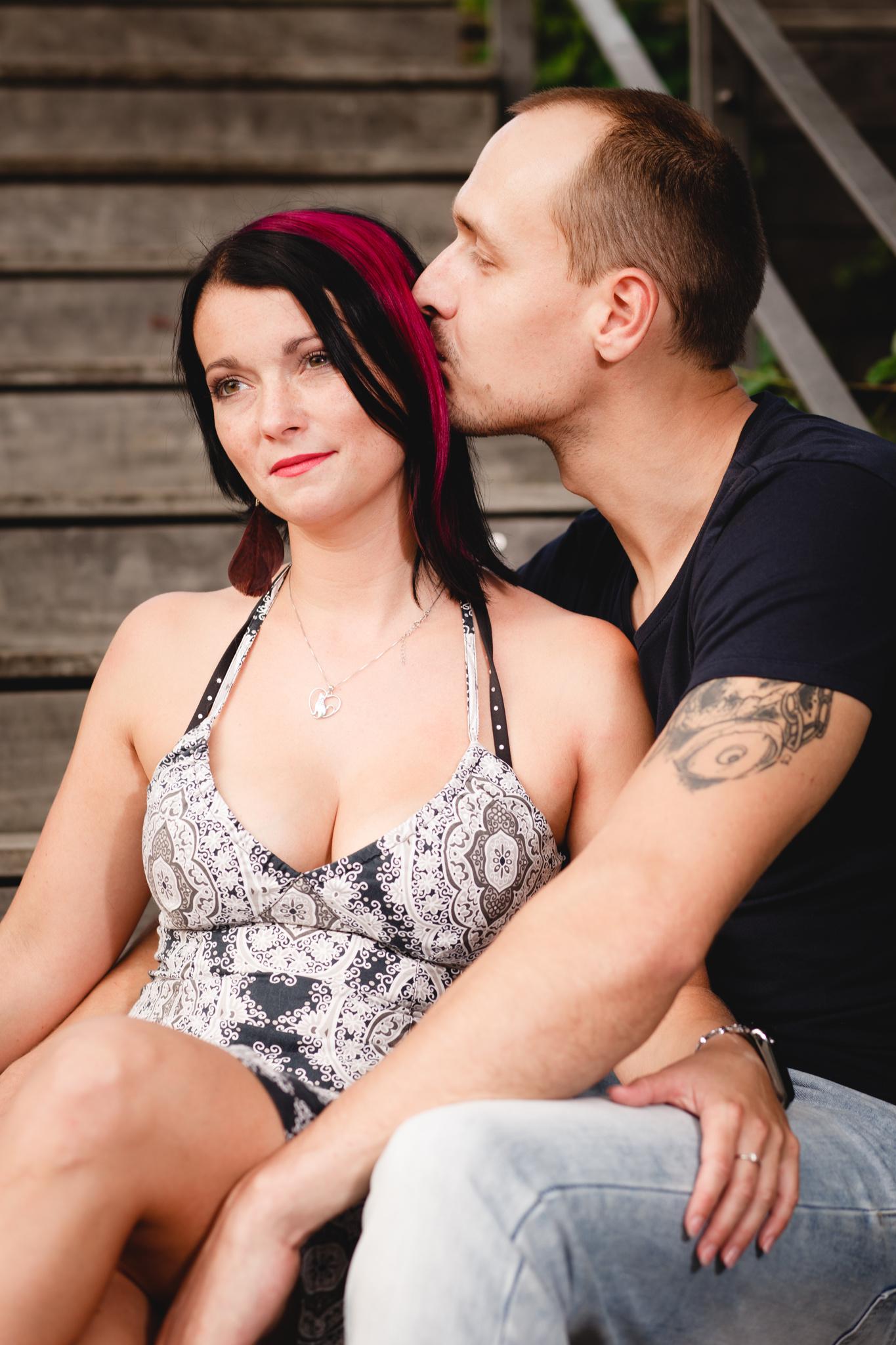Přítel dává pusu do vlasů přítelkyni, Partneři sedí u stromu, předsvatební focení, portrét
