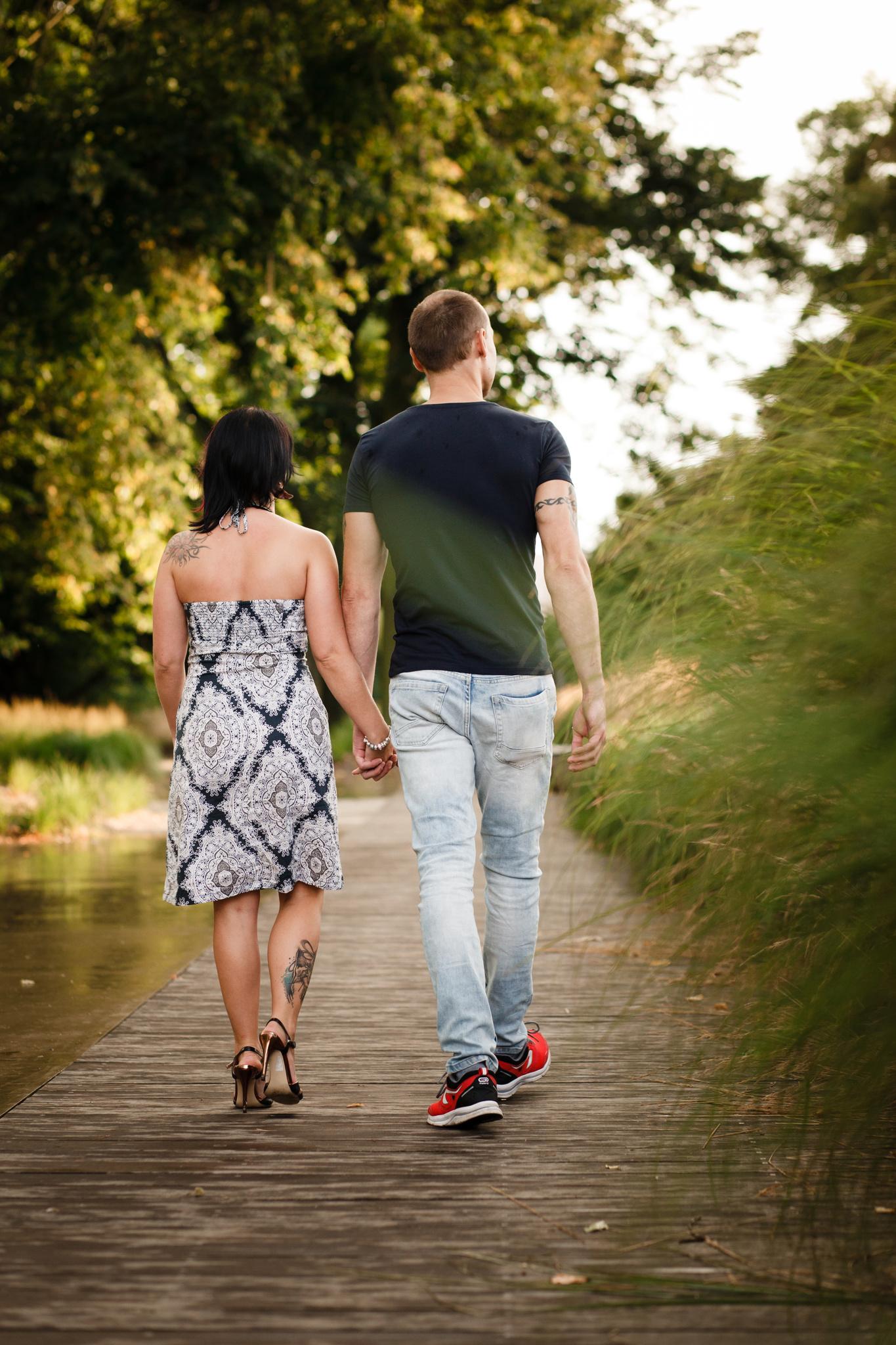 Přítel s přítelkyní jdou po cestě v parku