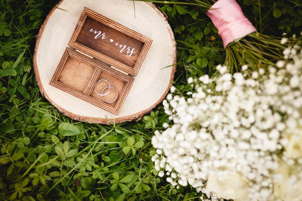 Detail na svatební prstýnky a kytici v trávě