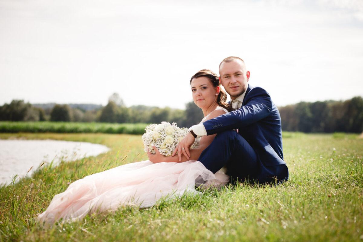 Nevěsta se ženichem sedí v trávě u rybníka, svatební portrét
