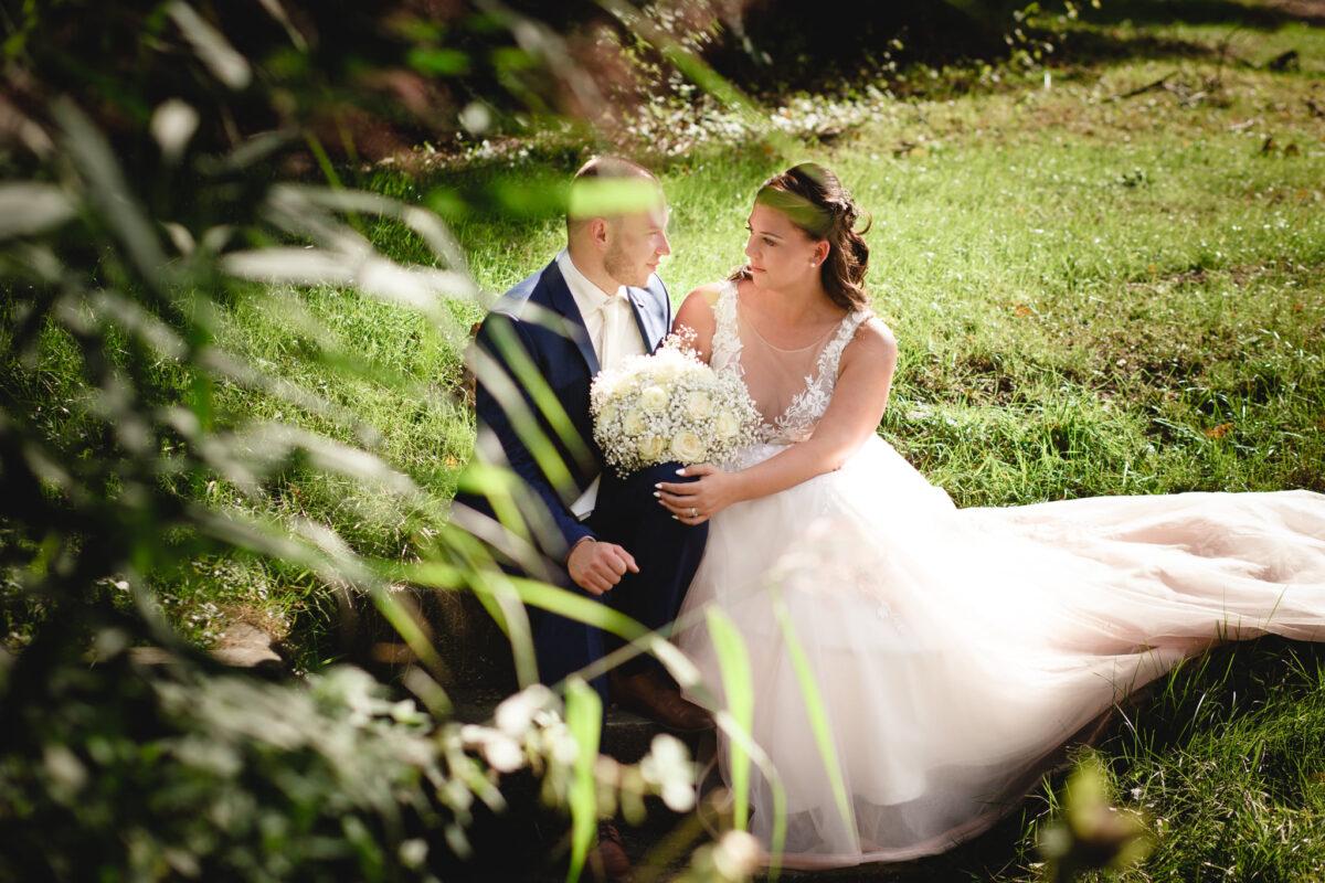 Svatební portrét, nevěsta sedí s ženichem v trávě