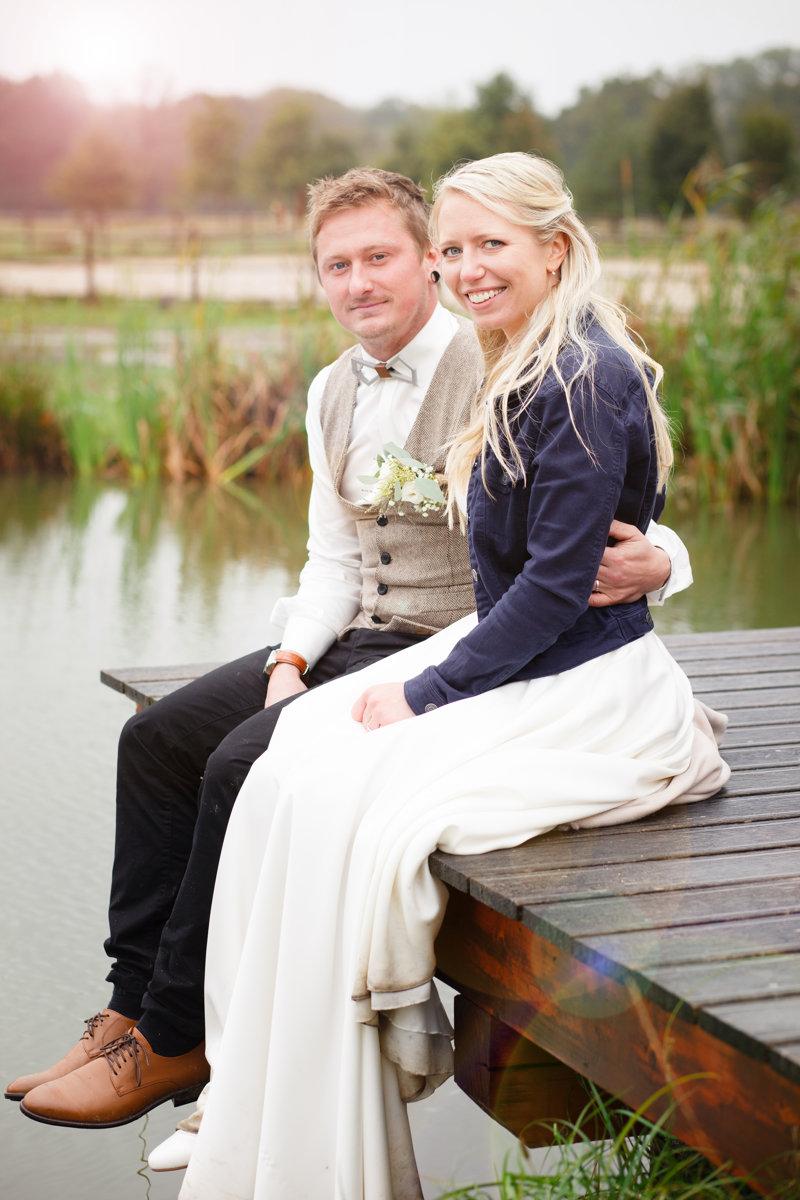 Nevěsta se ženichem sedí na mole rybníčka, svatební portrét, Ranč Orlice