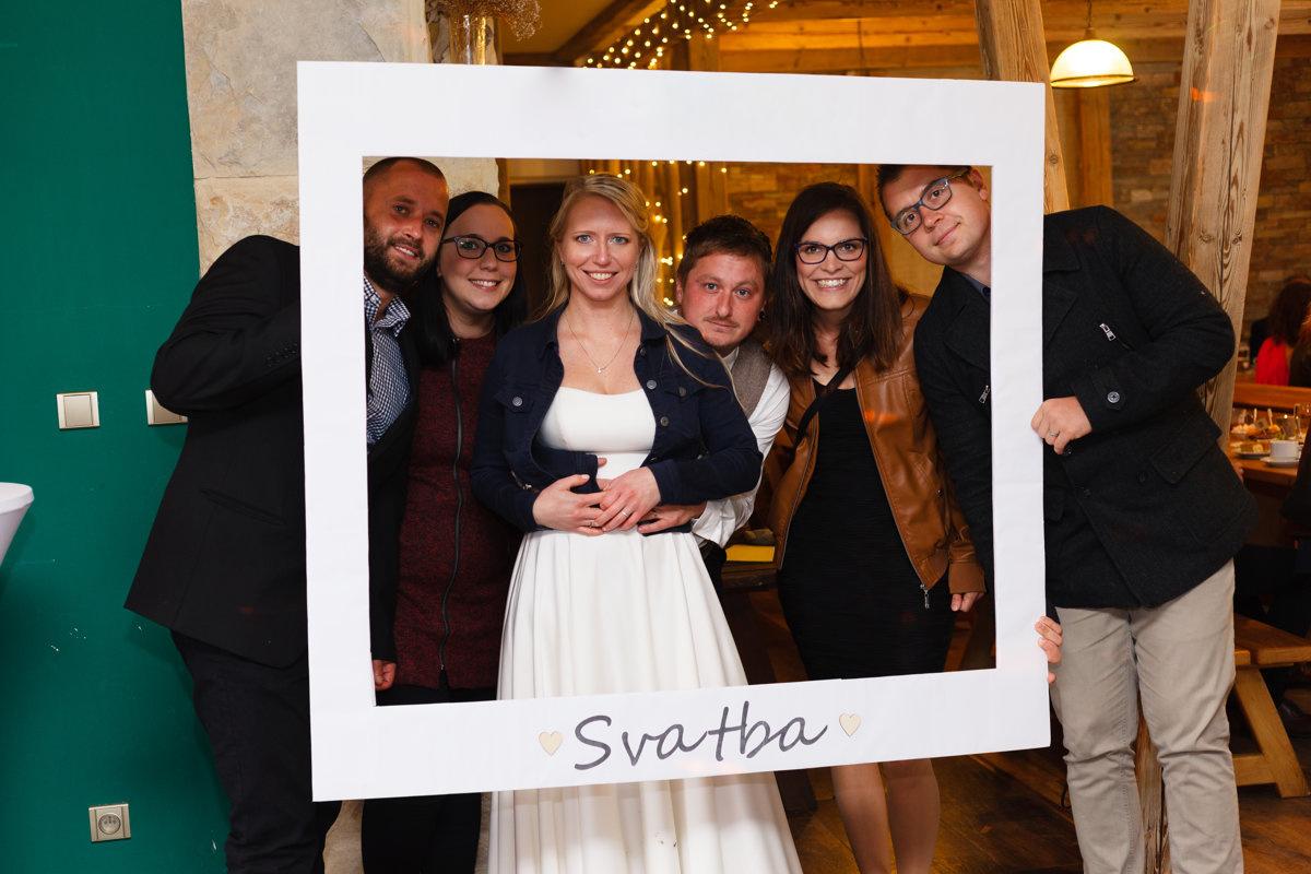 Nevěsta se fotí s kamarády ve svatební rámu