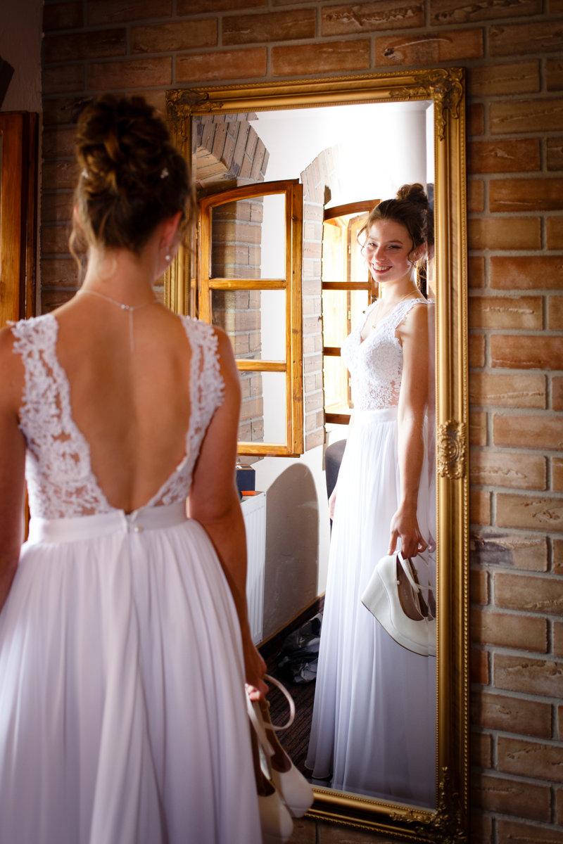 Nevěsta se dívá na sebe v zrcadle, svatba