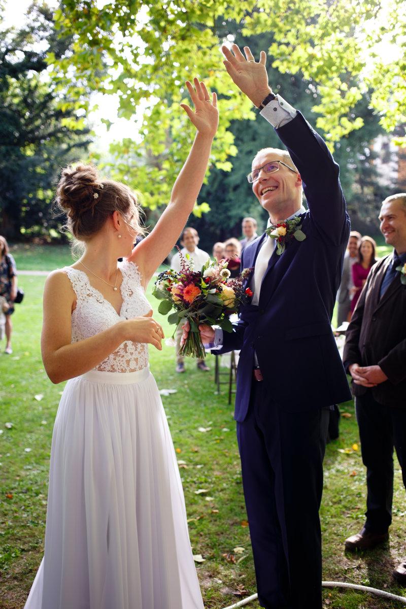 Nevěsta se ženichem ukazují svatebčanům prstýnky