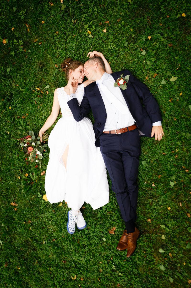 Svatební portrét, nevěsta se ženichem leží v trávě
