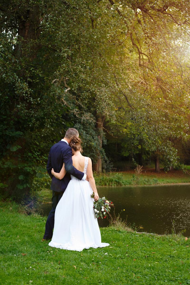Nevěsta se ženichem se objímají a koukají na rybník