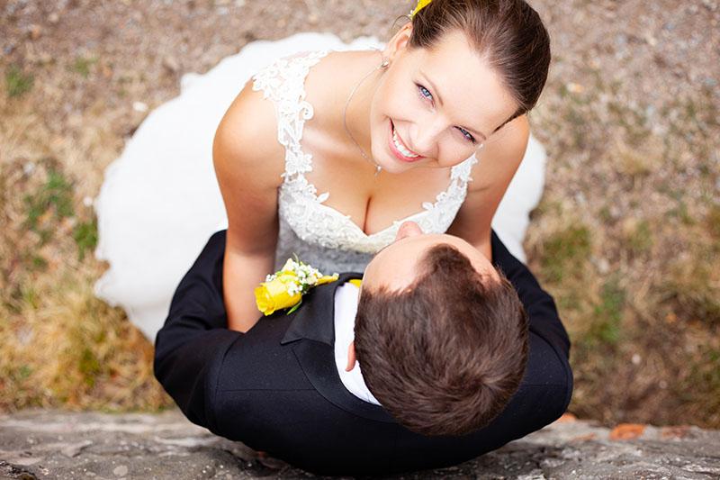 Nevěsta kouká na fotografa, zatímco jí ženich drží kolem pasu, portrét, svatba