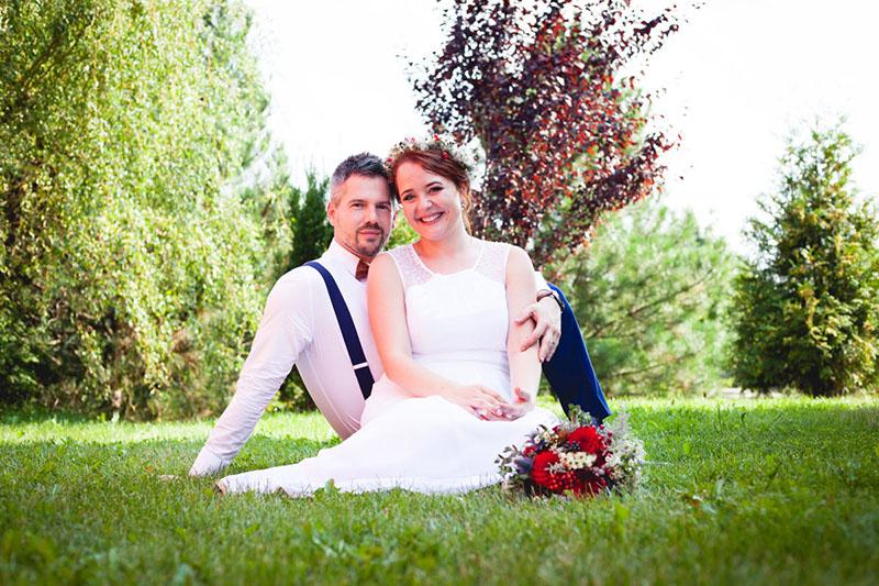 Portrét nevěsty a ženicha jak sedí v trávě