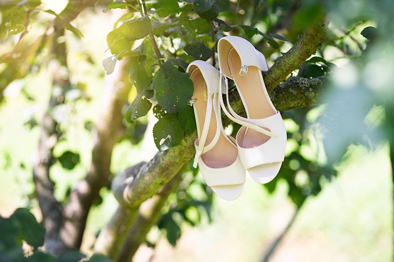 Detail na boty nevěsty jak visí na větvi stromu, svatba