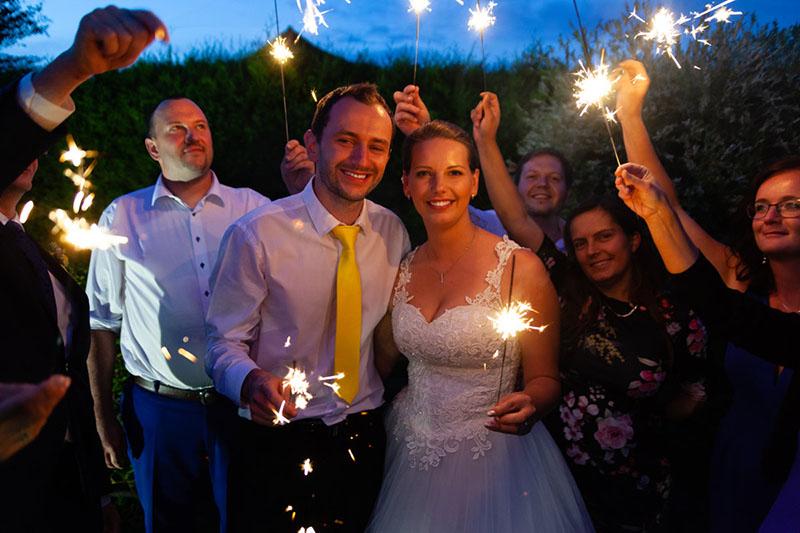 Portrét nevěsty a ženicha jak drží prskavky, svatba