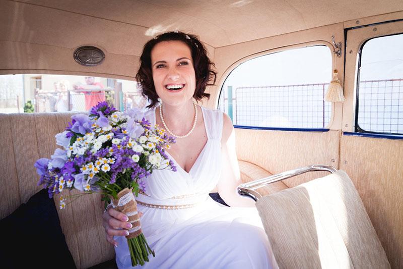 Nevěsta sedí ve veteránu a drží kytku, portrét, svatba
