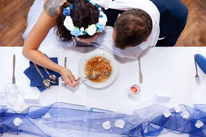 Portrét z vrchu, nevěsta se ženichem jedí polévku