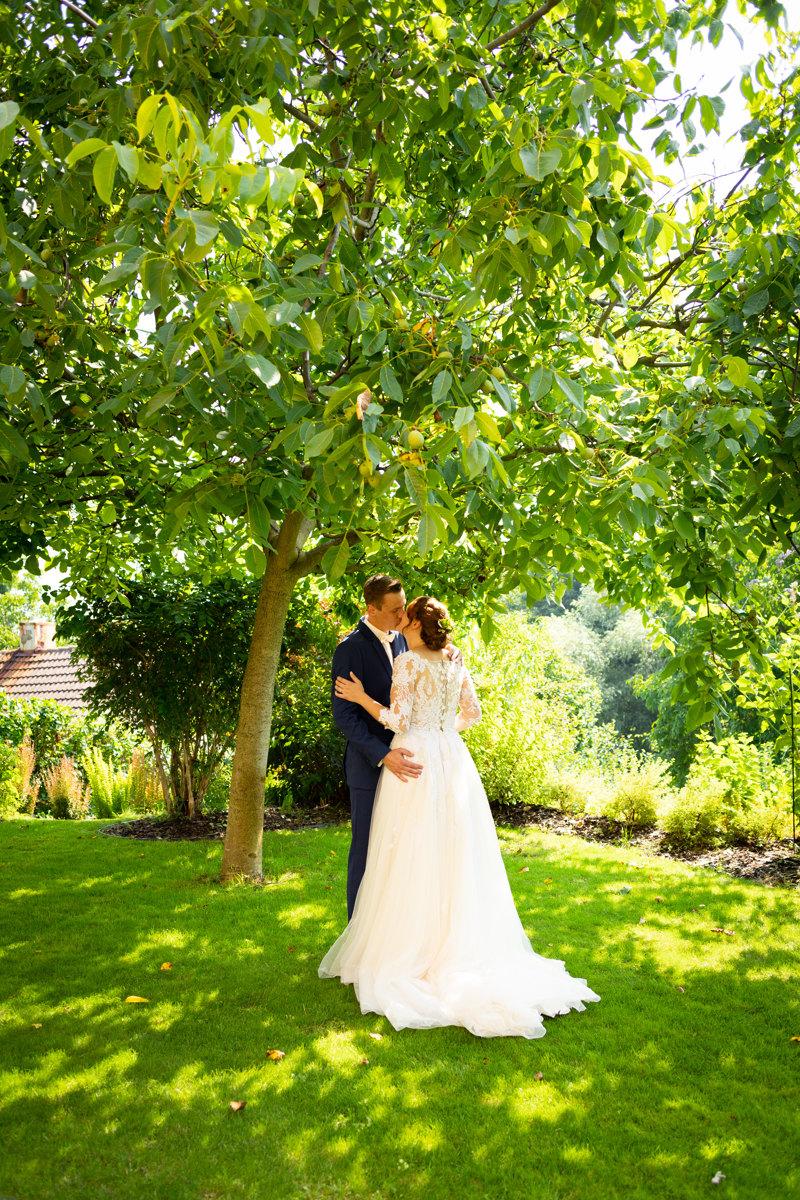 Nevěsta se ženichem se líbou pod stromem