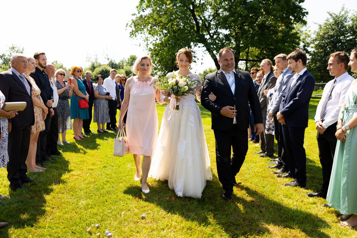 Nevěsta jde s rodiči k obřadu