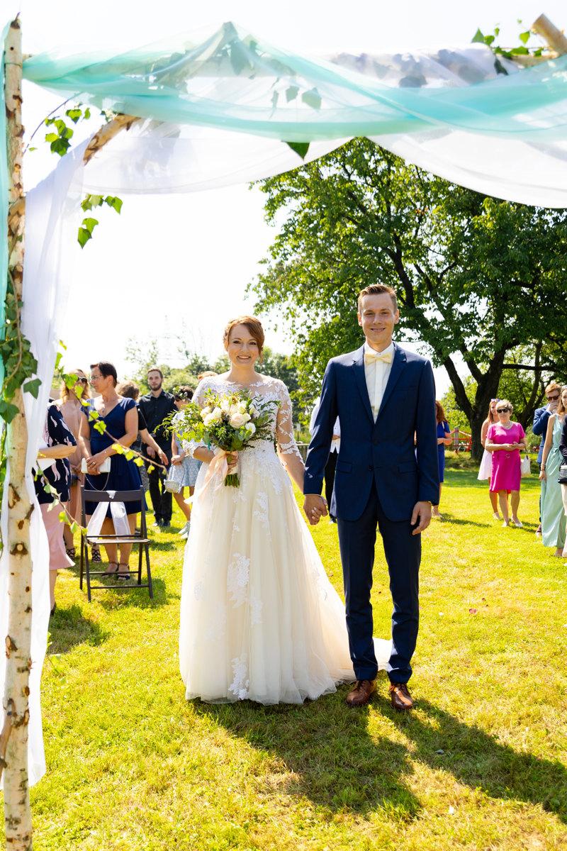 Nevěsta se ženichem stojí břed dřevěnou bránou, obřad, svatba