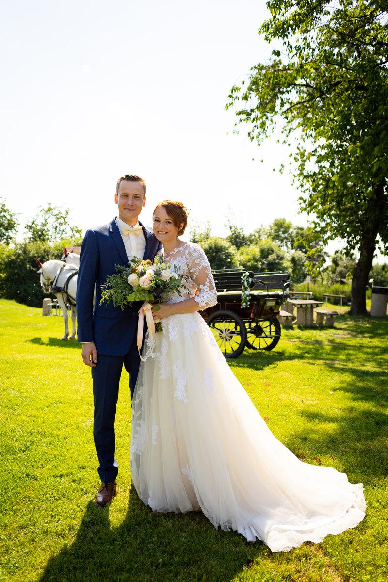 Portrét nevěsty a ženicha, jak stojí před kočárem