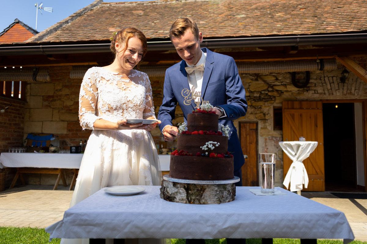 Nevěsta se ženichem zakrajují dort
