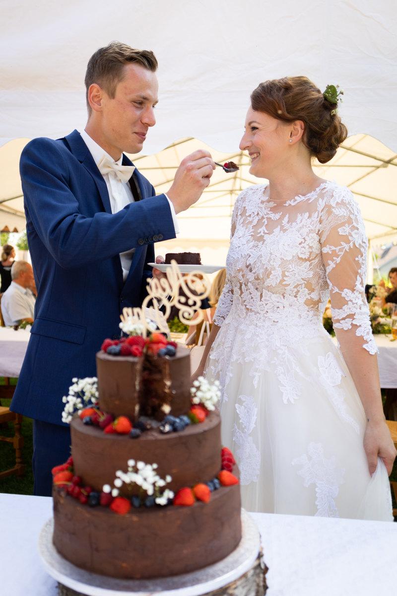 Ženich dává nevěstě ochutnat svatební dort