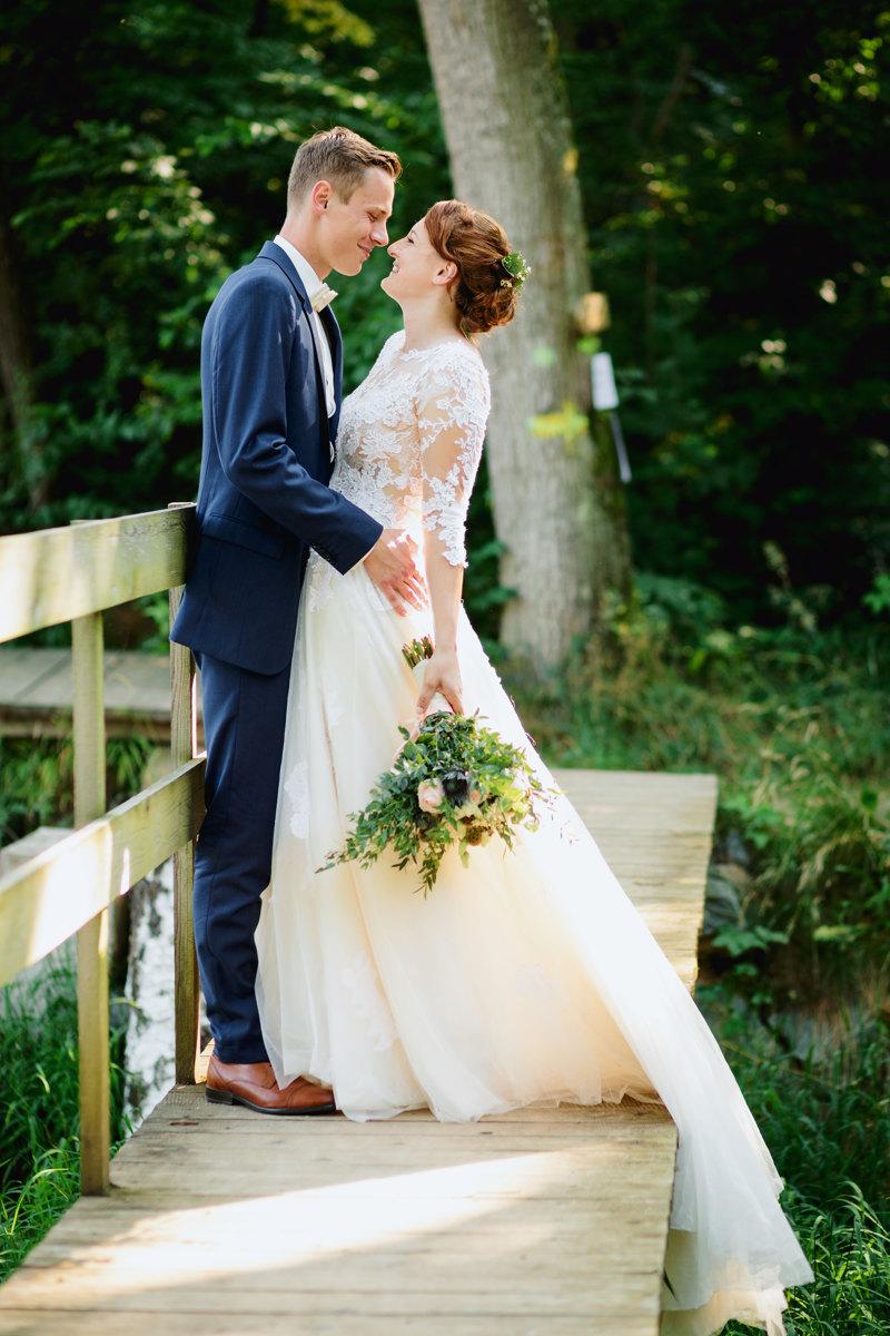 Nevěsta se ženichem stojí na dřevěném mostku a dívají se do očí