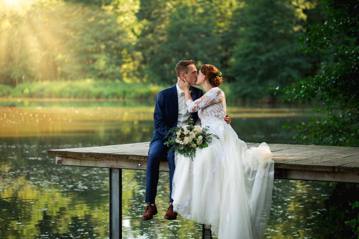 Portrét nevěsty a ženicha, jak sedí na mole rybníka a dávají si pusu
