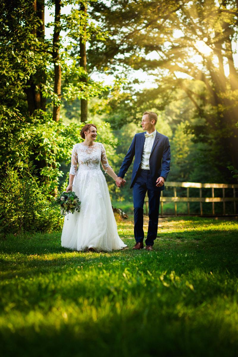 Nevěsta se ženichem se prochází v přírodě při západu slunce