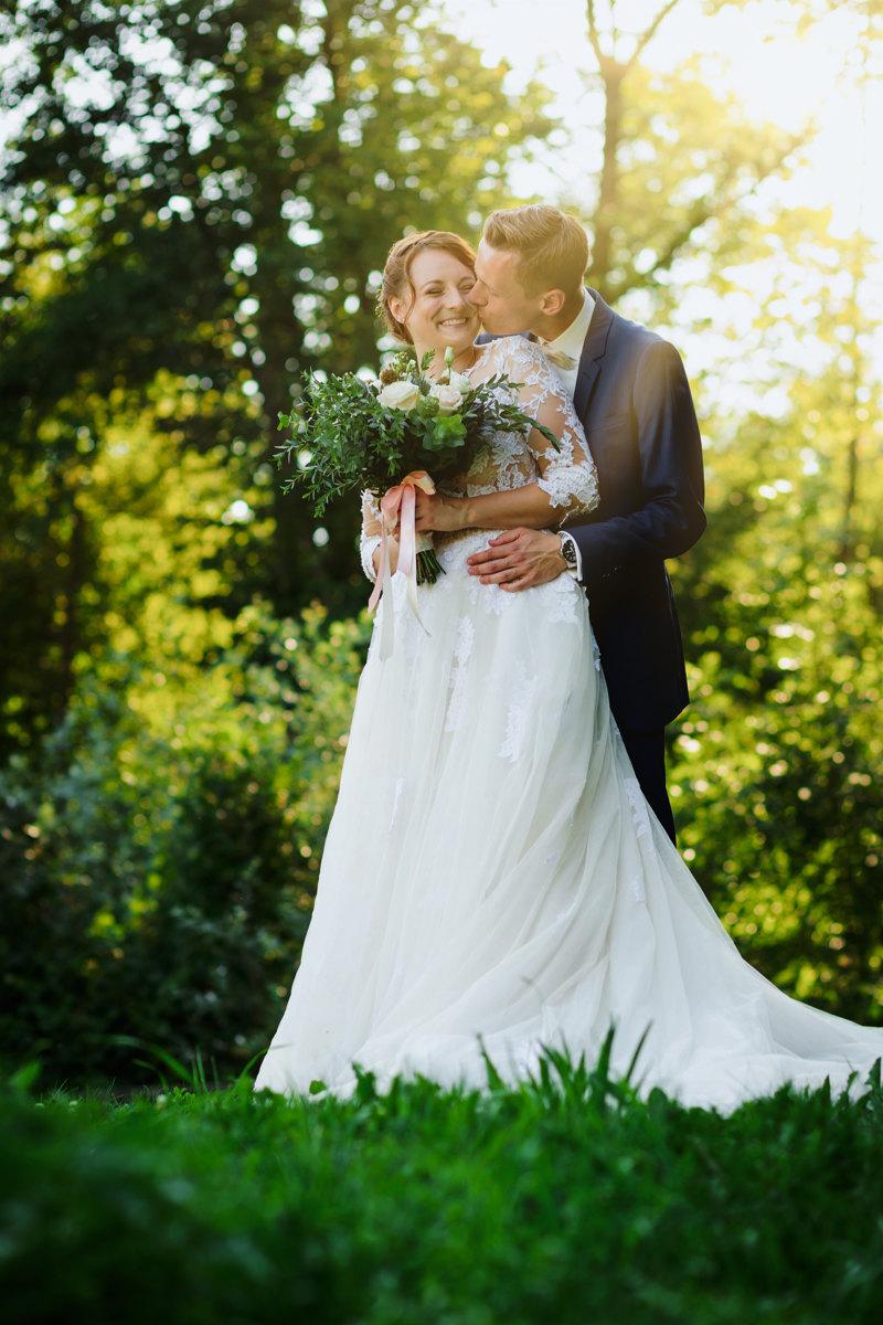 Svatební portrét, ženich objímá nevěstu a dává jí pusu