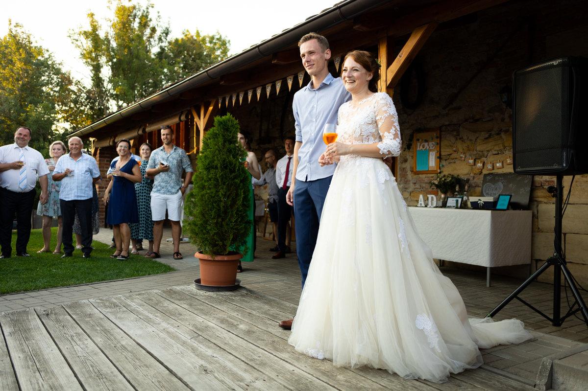 Nevěsta se ženichem stojí na parketu a smějí se