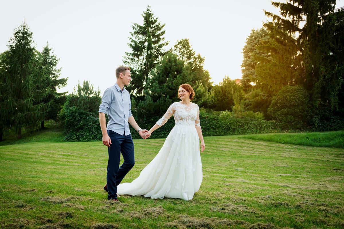 Nevěsta se ženichem se prochází po louce při západu slunce, portrét