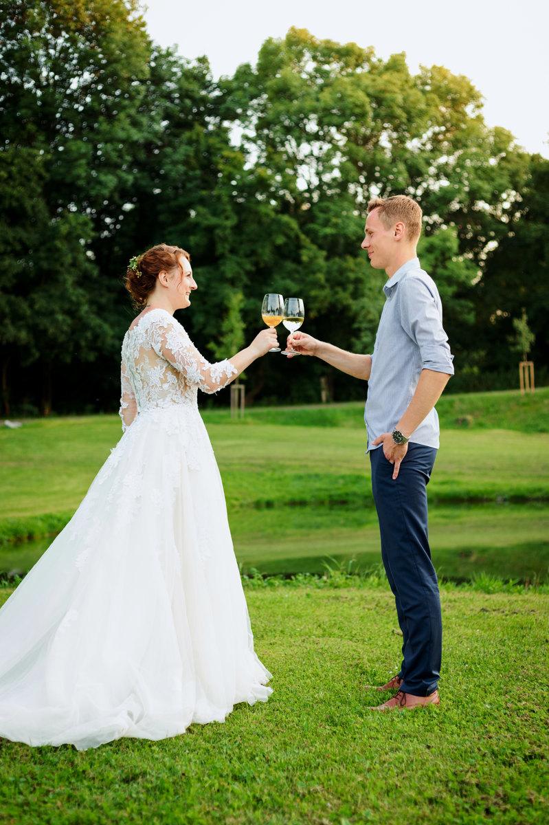 Nevěsta se ženichem si připíjejí na zdraví na louce, portrét
