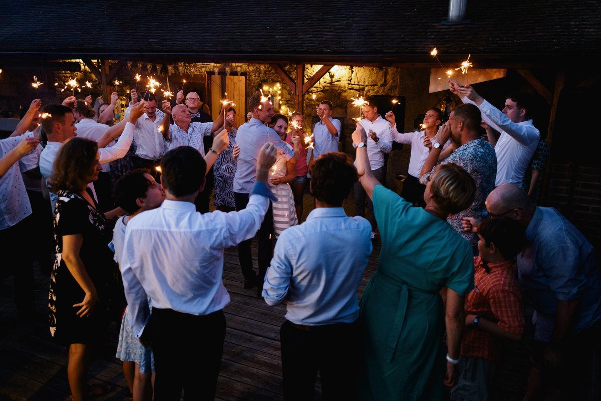 Svatba, nevěsta se ženichem tancuje s prskavkami, svatebčané v kroužku